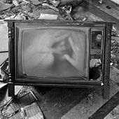stock photo of distortion  - A ghostly figure appears on the flickering screen of an old tv set - JPG