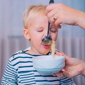 Mom Feeding Son. Boy Cute Baby Eating Breakfast. Child Eat Soup. Kid Cute Boy Blue Eyes Sit At Table poster