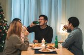 Merry Christmas And Happy New Year! Young Friends Group Having Dinner At Home. Asian Family Party Wi poster