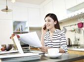 Happy Asian Young Asian Business Woman Working From Home Making A Call Using Cellphone poster