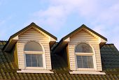 The Pair Of Windows Look Out From Steep Roof To Blue Skies. Two Attic Windows With White Frames On T poster