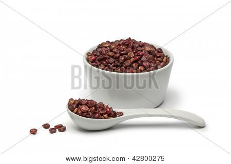Dried Sumac berries in a cup and spoon on white background