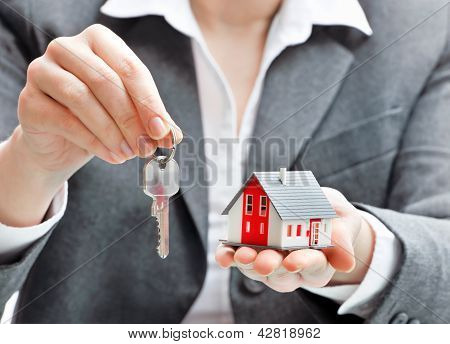 Businesswoman With House Model And Keys