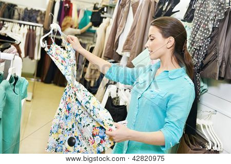Young woman choosing dress during clothing shopping at apparel store