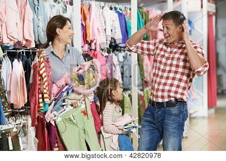 Família de compras. Mulher e menina segurando a roupa com homem pai altamente surpreendido durante as compras no