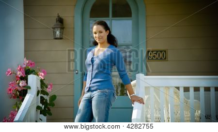 African American Woman Stands On Her Porch Smiling