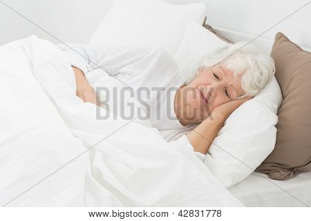 Aged woman sleeping on the bed