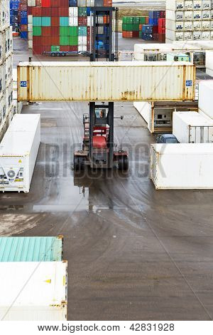 Forklift hauling a 45 foot container through the outdoors storage park of a large distribution center with reafers, containers at a large industrial harbour