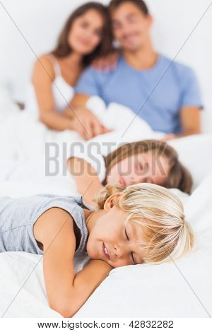 Sleeping children lying on the bed with their parents behind them