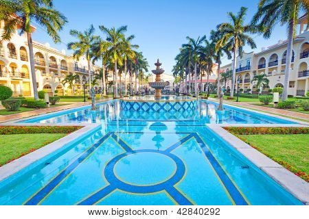 PLAYA DEL CARMEN, MEXICO - JULY 11, 2011: Scenery of luxury swimming pool at RIU Palace Hotel on July 11, 2011 in Playa del Carmen. RIU Hotels & Resorts has more than 100 hotels in 19 countries.