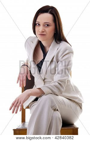 Gorgeous Businesswoman In White Suite Sitting On A Chiar Isolated Over White