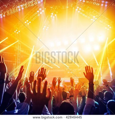 Picture of a lot of people enjoying night perfomance of famous dj, large crowd of youth dancing with raised up hands on rock concert, party in dance club, bright yellow light from stage, nightlife