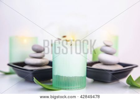 Photo of pebble stones in black bowls and candles isolated on white background, soft focus, beautiful still life, spa resort, body care, relaxation in massage salon, dayspa, organic cosmetics