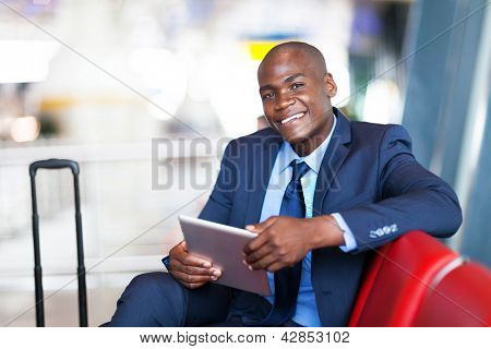 african business traveller using tablet computer at airport