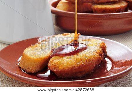 closeup of a plate with some torrijas, typical spanish dessert for Lent and Easter, with honey