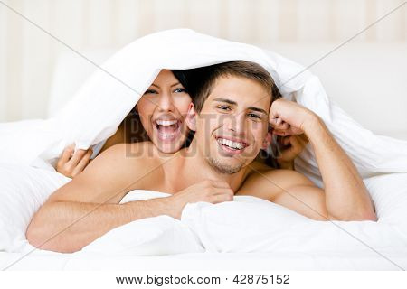 Close up of couple playing in bed. Covered with blanket woman lying on the back of the man