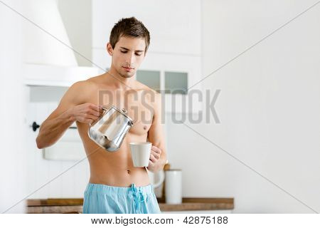 Half-naked male pouring coffee at the kitchen, having breakfast