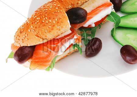 salmon sandwich and olives on green dish