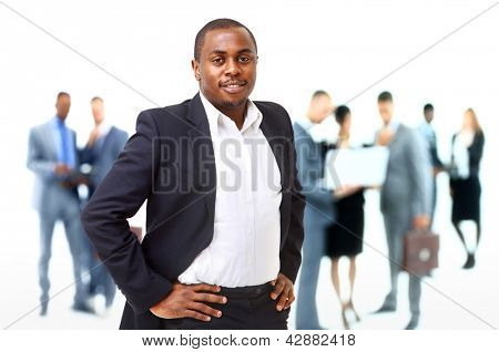 Portrait of smart African American business man smiling with colleagues in background