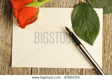 BLANK CARD AND A RED ROSE