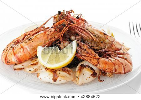 Jumbo prawns and grilled squids with black rice isolated on white background