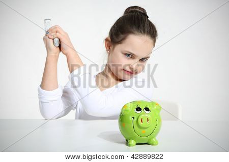 Small girl breaking piggy bank
