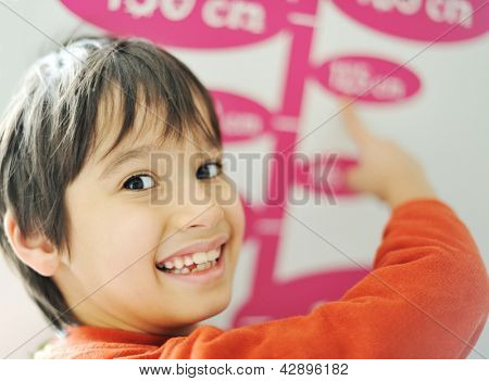 Boy growing tall and measuring his height on the wall
