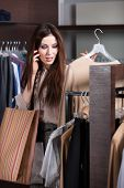 Speaking on the mobile phone and choosing clothes in the store