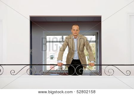 Portrait of a business man leaning on a handrail