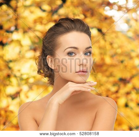 health and beauty concept - face and hands of beautiful woman with updo over yellow autumn leaves background