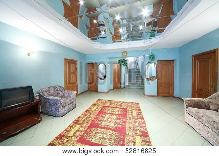 Hallway with chair, sofa, carpet on the floor and five doors