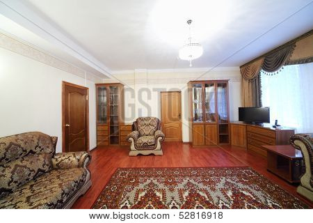Living room with sofa, chairs, sideboard and a carpet on the floor