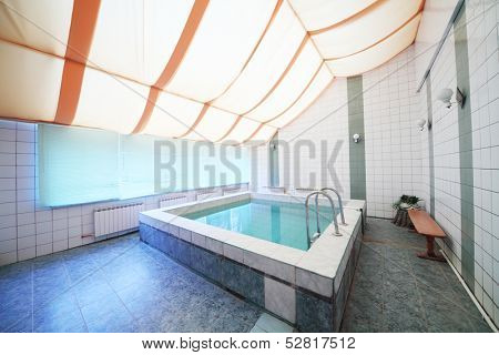A small indoor pool with tiles on walls and floor and blinds on the windows