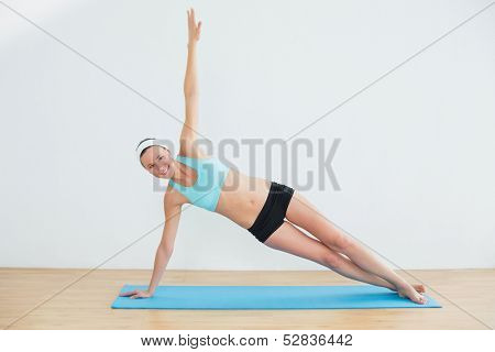 Full length portrait of a slim young woman doing the side plank yoga pose in fitness studio