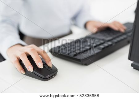 Close-up of hands computer keyboard and mouse in an office