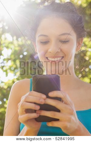 Content young woman dialing with her smartphone in a park