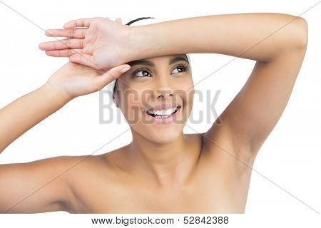 Smiling nude brunette with hairband touching forehead on white background
