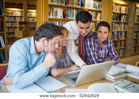 Mature students sitting at the library while looking at teacher use a laptop