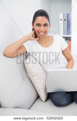 Gleeful young woman using her notebook sitting on couch smiling at camera