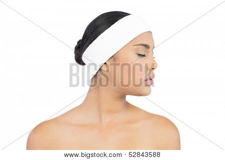 Calm nude brunette with hairband closing her eyes on white background