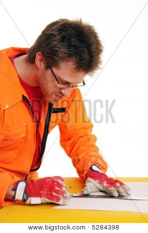 Worker In Orange Workwear Measuring With A Ruler