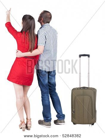young traveling couple with suitcas pointing at wal. Back view. Rear view people collection. backside view of person. Isolated over white background