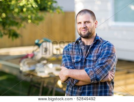 Portrait of confident mid adult manual worker with arms crossed standing at construction site