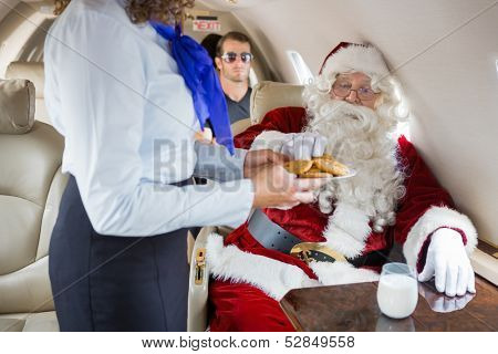 Stewardess serving Santa cookies with body guard in background.