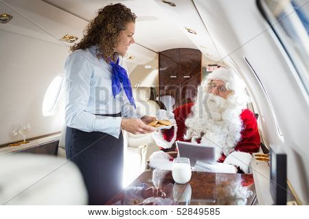 Mid adult smiling airhostess serving cookies to Santa in private jet