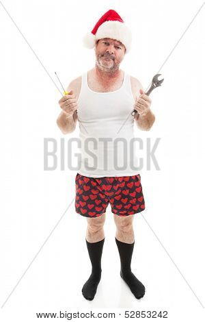 Frustrated dad in a Santa hat holding his tools.  He looks scruffy, like he's been up all night assembling Christmas presents.  Full body isolated on white.