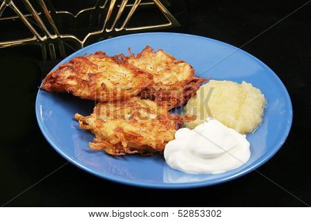 "A plate of delicious potato pancakes, or ""latkes"" for Hanukkah,  with the traditional garnish of sour cream and applesauce.  Black background with menorah."