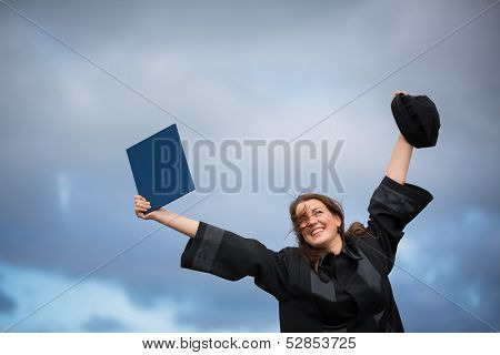 Pretty, young woman celebrating joyfully her graduation - spreading wide her arms, holding her diploma, savoring her success (color toned image; shallow DOF)