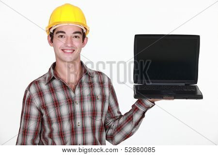 Young laborer holding laptop