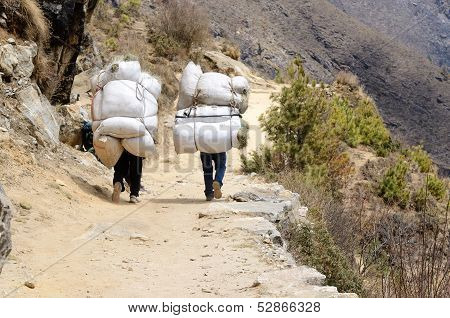 Two Sherpa Porters Carrying Heavy Sacks In The Himalaya At Everest Base Camp Trek ,Nepal